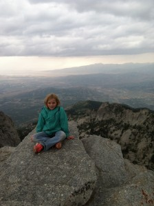 The author's daughter precariously perched on the 11,253 foot summit of Lone Peak