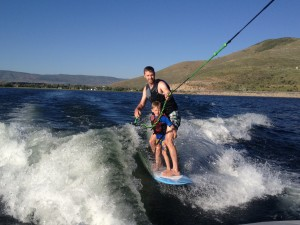 Surfing with my son behind the new fancy boat